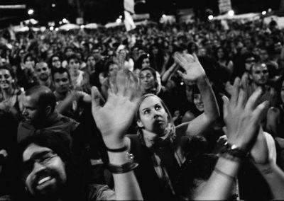 """L'esplosione. Durante le marce del 15 Maggio un gruppo di attivisti: """"Democracia real Ya"""" decide di fare un accampamento di protesta nella piazza più visibile di Madrid, Puerta do Sol. Cacciati la notte dalla polizia, occupano nuovamente la piazza il giorno dopo. Il 16 Maggio cominciano così nuove occupazioni anche a Barcellona e Valencia. Quando migliaia di persone sfidano la scelta del governo di soffocare le proteste nasce: """"#acampadasol"""" a Madrid e Barcellona e in meno di una settimana si formano cinquantacinque """"acampadas"""" in tutta la Spagna. Plaza Catalunya diventata il centro nevralgico permanente di tutta la protesta a Barcellona. """"AcampadaBcn"""" è una piccola cittadella di pensiero indipendente nella quale la sera dopo il tramonto avvengono le assemblee cittadine dove si decidono le azioni massive e pacifiche."""